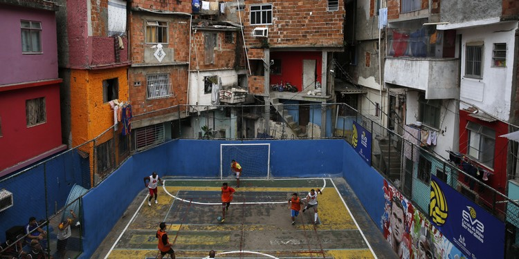 People take part in a soccer match held at the Tavares Bastos slum in Rio de Janeiro May 18, 2014. The World Cup will be held in 12 cities in Brazil from June 12 till July 13. REUTERS/Pilar Olivares (BRAZIL - Tags: SPORT SOCCER TPX IMAGES OF THE DAY) - RTR3PPVQ